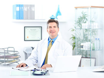 Handsome medical doctor working in the office. Health care.